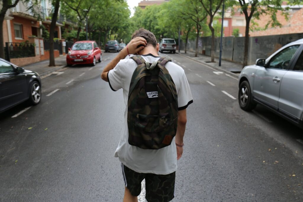 teenager walking down street with backpack